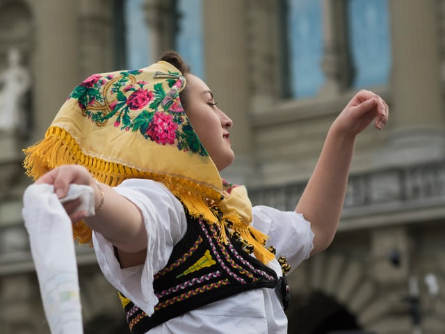 Eine junge Frau in albanischer Tracht tanzt vor dem Bundeshaus.