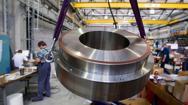 Grosses, rundes Stahlelement hängt an Gurten in einem Produktionshalle.