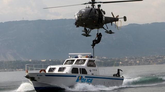 Von einem Helikopter seilt sich ein Polizist in ein Schiffab.