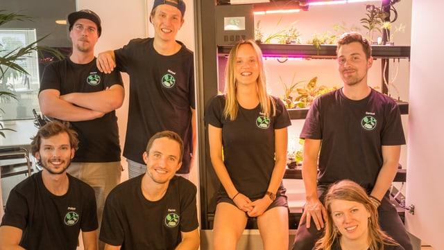 Ein Gruppe von sieben Personen steht und kniet vor einem schwarzen Gerät, in dem Pflanzen wachsen.