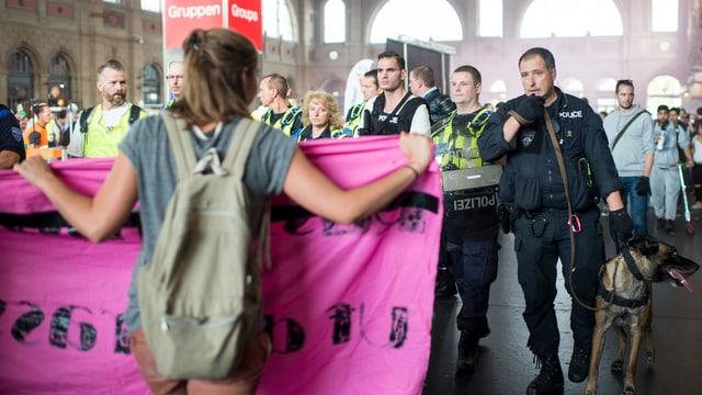 Eine Frau hält ein pinkes Banner in der Halle des Zürcher HB, dahinter Polizisten mit einem Hund.