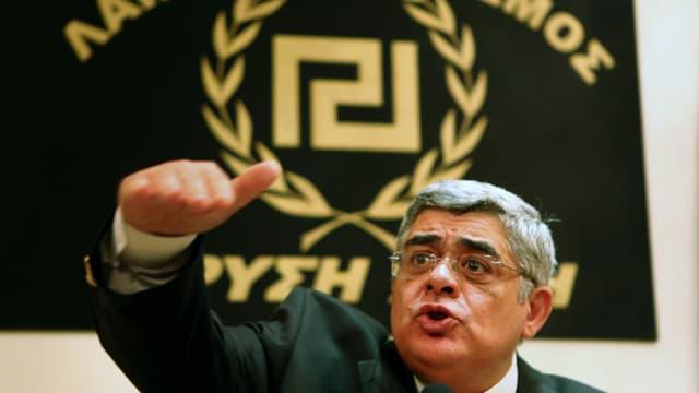 Mann unter einem Partei-Logo mit der Hand gestikulierend.