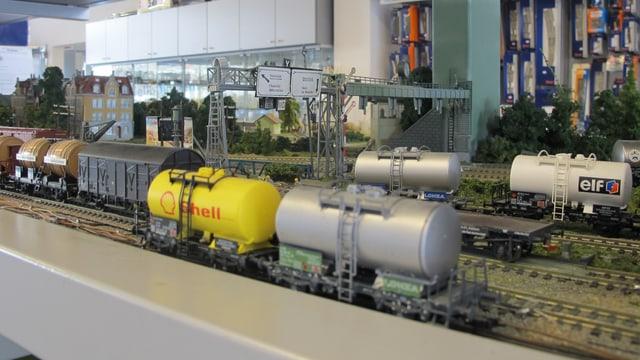 Güterbahn-Wagen in einer Modellbau-Landschaft mit mehreren Gleisen und Häusern im Hintergrund.