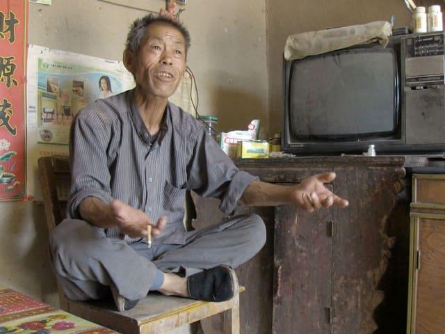 In einem staubigen und kargen Zimmer sitzt ein älterer chinesischer Mann im Schneidersitz auf einem Stuhl, sprechend, mit Zigarette in der Hand.