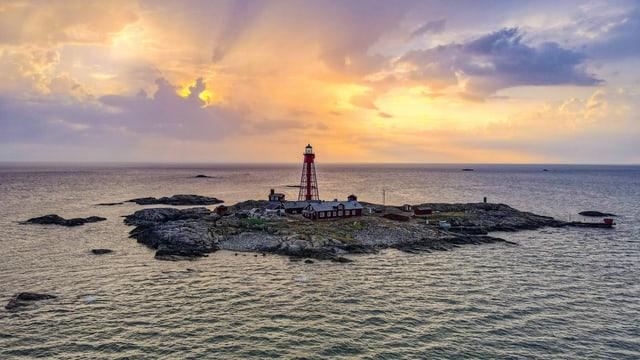 Einsame Insel im Sonnenuntergang mit Leuchturm und Haus