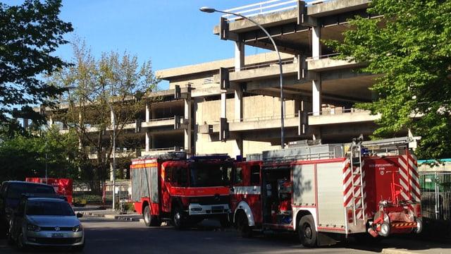 Zwei Feuerwehrautos vor einem ausgehölten Gebäude.