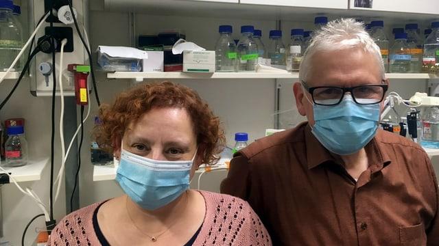 Eine Frau und ein Mann in einem Labor. Sie tragen Schutzmasken