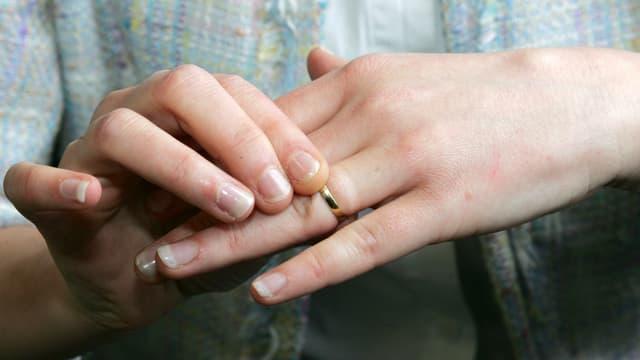 Zwei Frauenhände, wobei die eine Hand den Ehering an der anderen auszieht.
