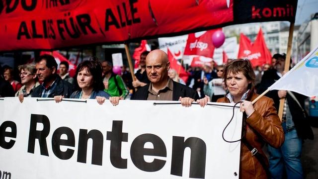 """Weisses Plakat mit Aufschrift """"Renten"""", dahinter marschieren viele Menschen."""