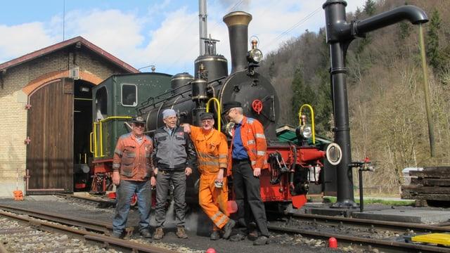 Dampflokomotive vor einer Lokremise mit vier posierenden Männern