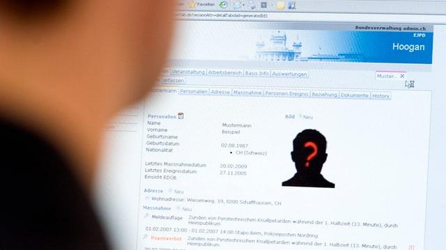 Mann schaut in Computer, auf dem Bildschirm die Hooligandatenbank mit Phantombild
