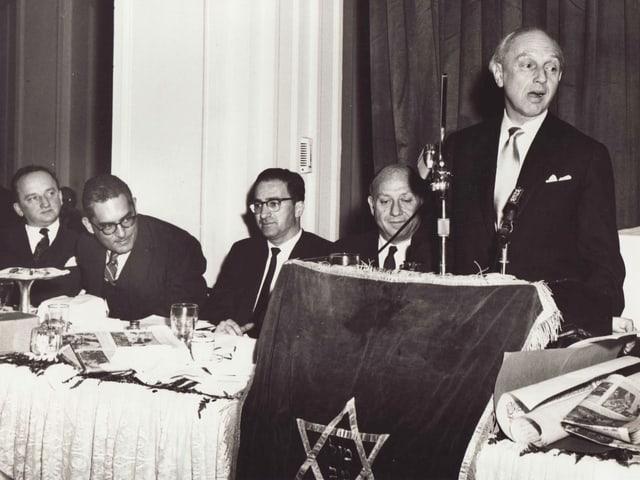 An einem Prozess steht ein Mann an einem Mikrofon, neben ihm sitzen vier Herren.