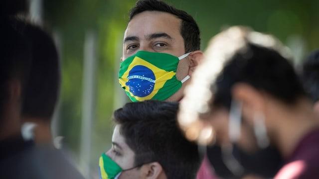 Ein Mann mit einer Maske mit Brasilien-Flagge