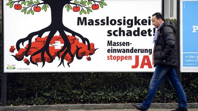 Ein Mann läuft vor einem Plakat der Masseneinwanderungsinitiative vorbei