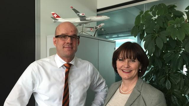 Ein Mann mit weissem Hemd und eine Frau in grauem Blazer stehen in einem Büro vor einer Pflanze und einem Modell eines Swiss-Flugzeugs.