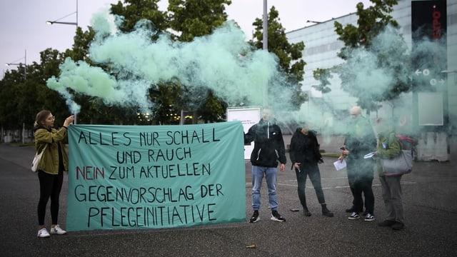 Rauchpetarden in grün und ein Banner, wo drauf steht: «Nein zum Gegenvorschlag»