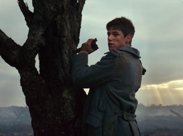 Mann steht vor Baum.