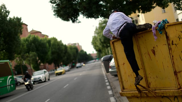 Ein Mann hängt an einer Mülltonne