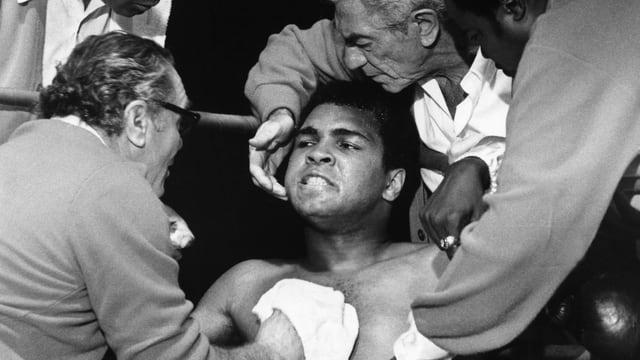 Ein Boxer hängt in der Ecke, das Gesicht verbissen. Viele Männer um ihn geschart.