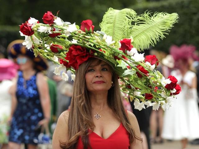 Eine Frau mit einem Hut, der an einen Blumenkranz aus Rosen erinnernt.
