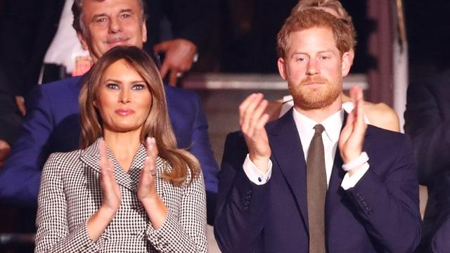 Melania Trump und Prinz Harry klatschend auf der Tribühne.