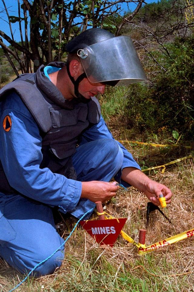 Ein Arbeiter im blauen Schutzanzug entschärft eine Mine.