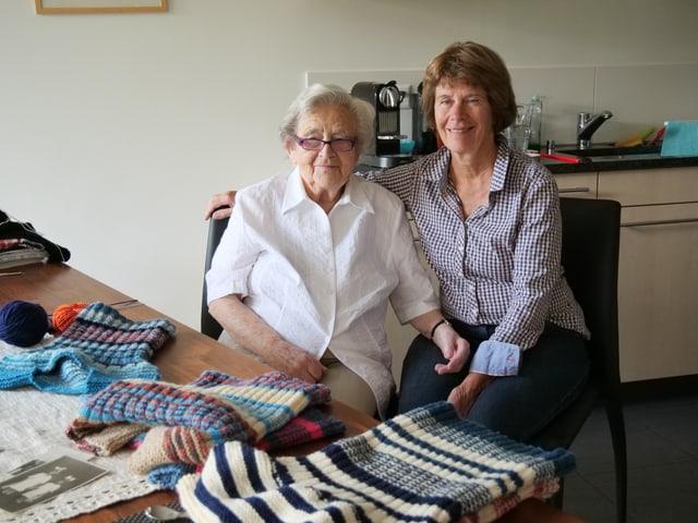 Zwei Frauen an einem Esstisch mit Strickarbeiten.