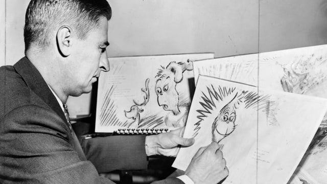 Ein altes schwarz-weiss-Foto. Darauf zu sehen: Ein Mann im Anzug, der an einem Tisch sitzt. Er hält ein Blatt in der Hand und zeichnet an einem Fantasietier. Auf dem Tisch verstreut liegen weitere Skizzen.
