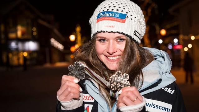 Corinne Suter zeigt ihre zwei Medaillen an der Weltmeisterschaft in Are.
