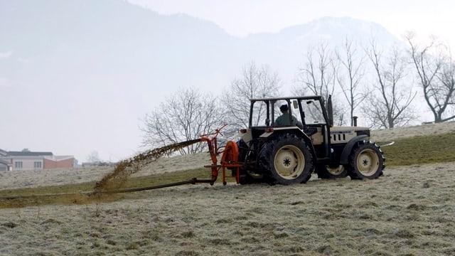 Ein Bauer trägt Gülle aus.