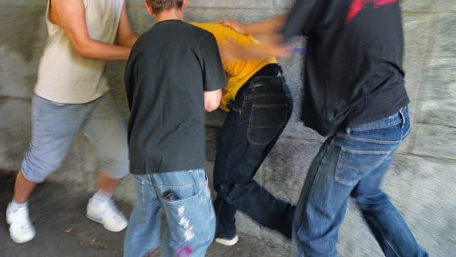 Jugendliche greifen einen jungen Mann an.