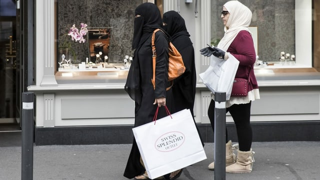Drei Touristinnen, zwei davon mit Nikab, mit Einkaufstaschen