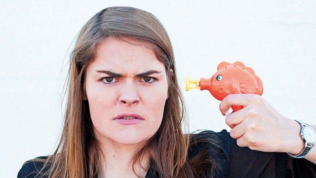Hazel Brugger mit einer Wasserspritzpistole am Kopf