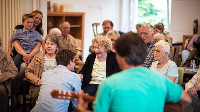 Vornehmlich ältere Menschen sitzen auf Stühlen. Ein Mann kniet vor einer älteren Frau, ein anderer Mann spielt Gitarre.