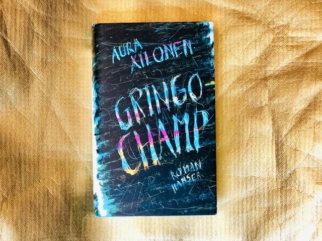 Der Roman «Gringo Champ» von Aura Xilonen vor goldigem Hintergrund