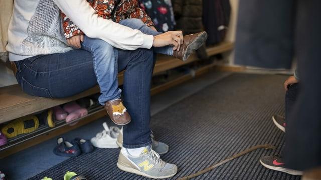 Eine Mutter zieht ihrem Kind in einer Kindertagesstätte die Schuhe an