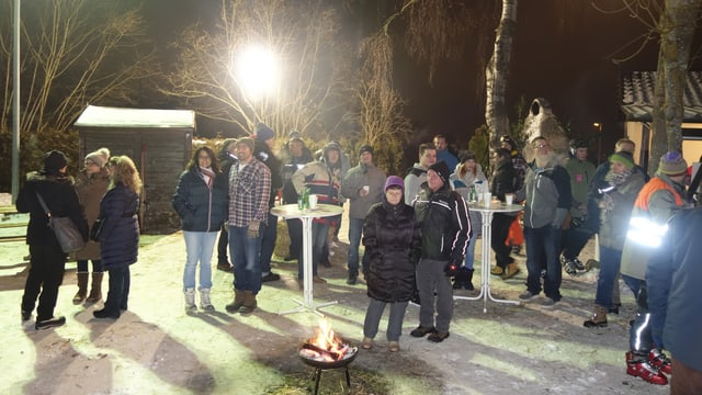 Menschen stehen um Bistotische, ein Feuer brennt in einer Schale, zufriedene Gesichter.