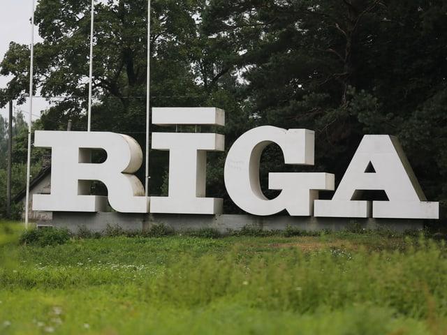 Auf einer Wiese bilden grosse, weisse Buchstaben das Wort «Riga».