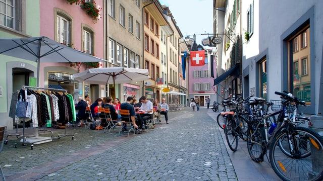 Blick in Aarauer Altstadtgasse. Menschen sitzen draussen und essen in einem Strassencafé.