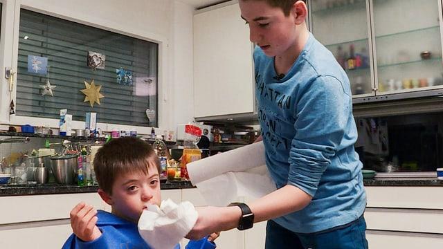 Joël putzt seinem Bruder die Nase.