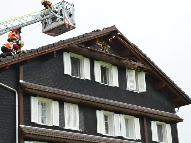 Ein Haus weist unter dem Dach ein Loch auf.