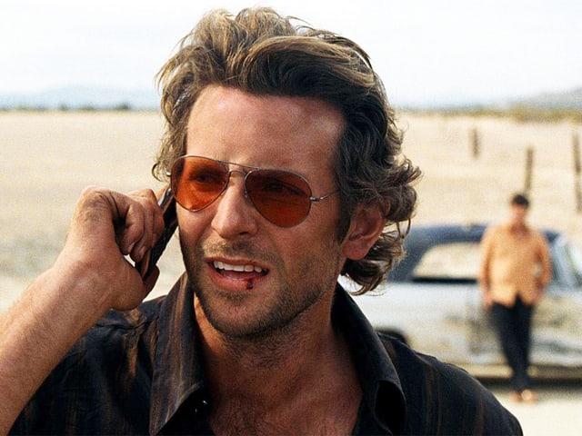 Bradley Cooper am Telefon in der Wüste.
