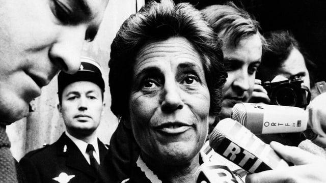 Schwarz-Weiss-Bild: Eine Frau um die sechzig, umringt von Mikrofonen.