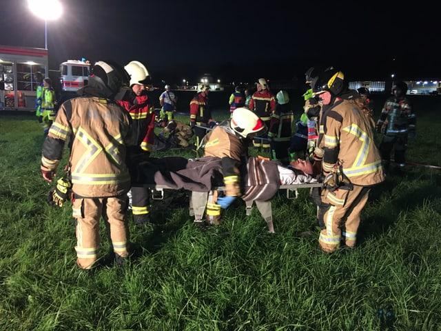 Feuerwehrleute tragen Verletzten
