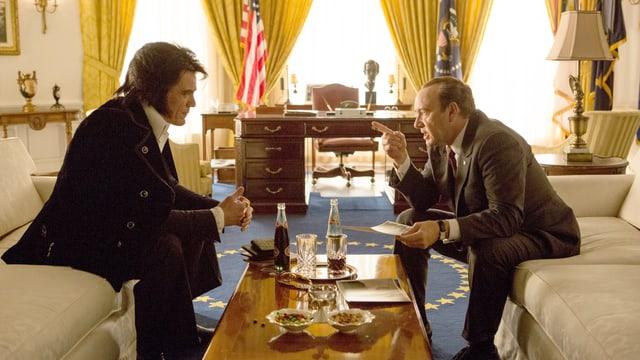 Elvis Presley und Richard Nixon sitzen zusammen im Oval Office auf weissen Sofas.