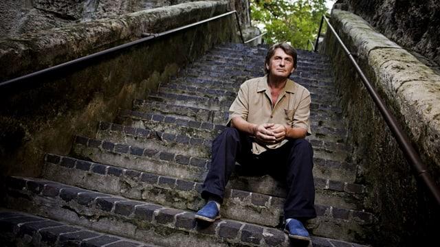 Mike Oldfield sitzt auf einer Steintreppe