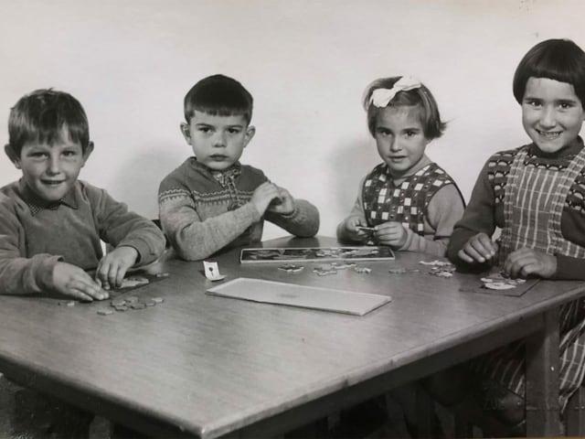 Zwei Buben und zwei Mädchen an einem Tisch.