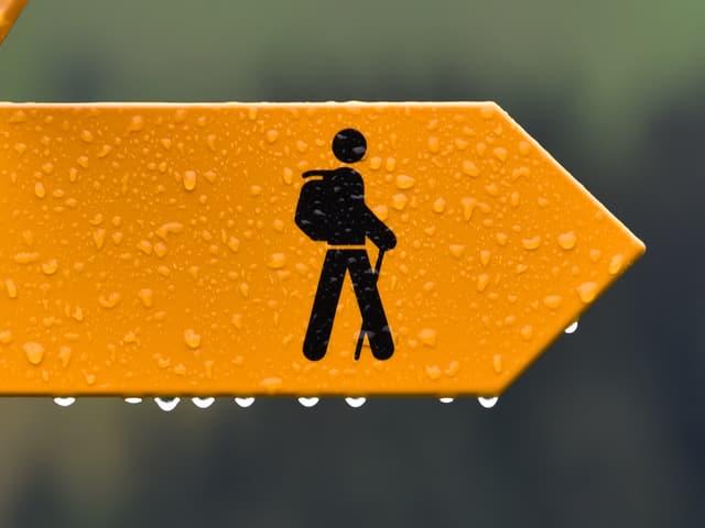 Ein gelber Wegweiser im Regen.