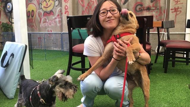Eine chinesische Frau mit zwei Hunden.