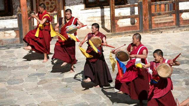 Männer in buddhistischer Kleidung mit Trommeln